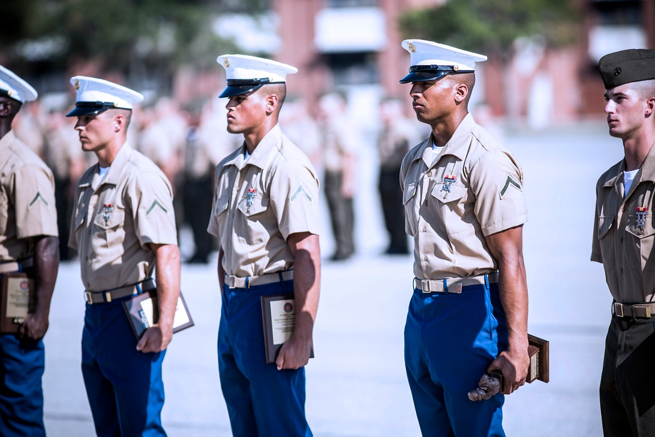 Marines standing at attention while holding awards and certificates.