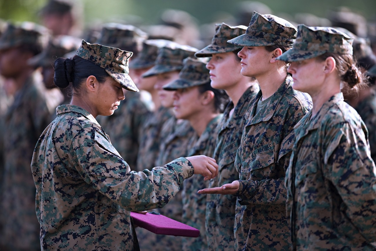 Marines receiving emblems during a graduation ceremony.