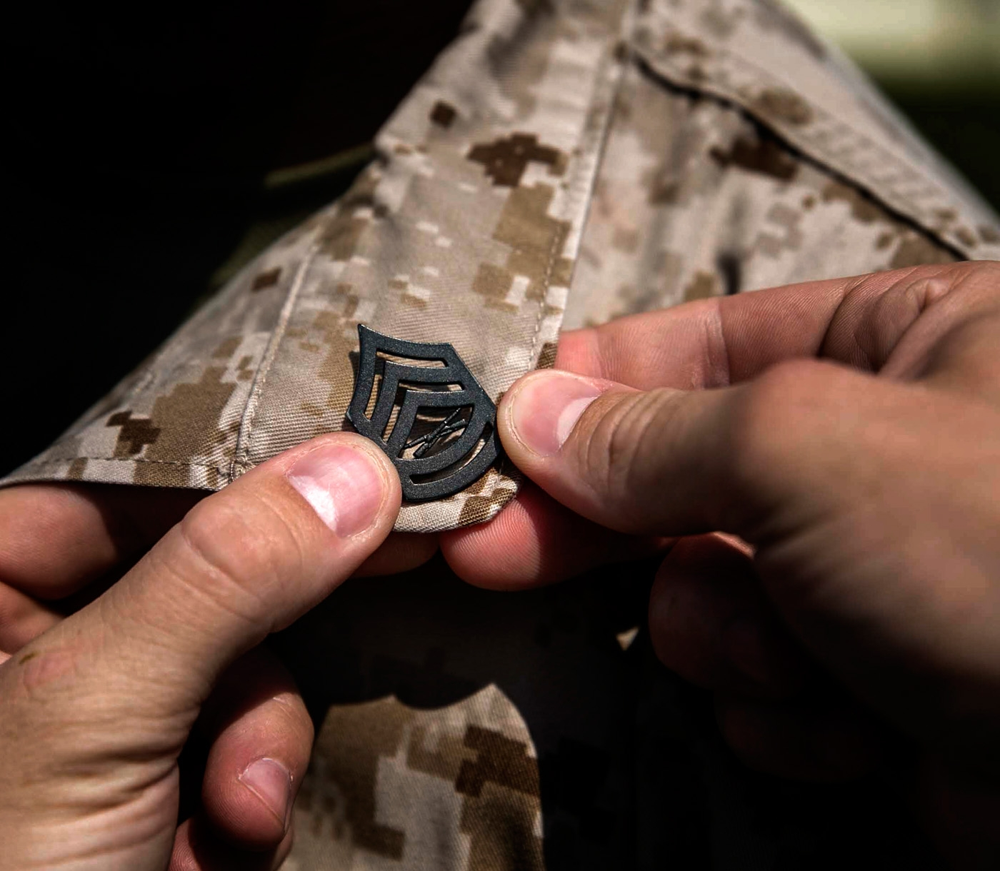 A Gunnery Sergeant pin is attached to a Marines cammies.