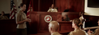A Marine Judge Advocate presents to other uniformed Marines in a court room.