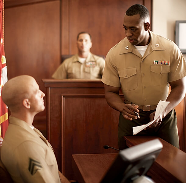 A Marine Corps Judge Advocate approaches a witness in a courtroom, paper in hand.