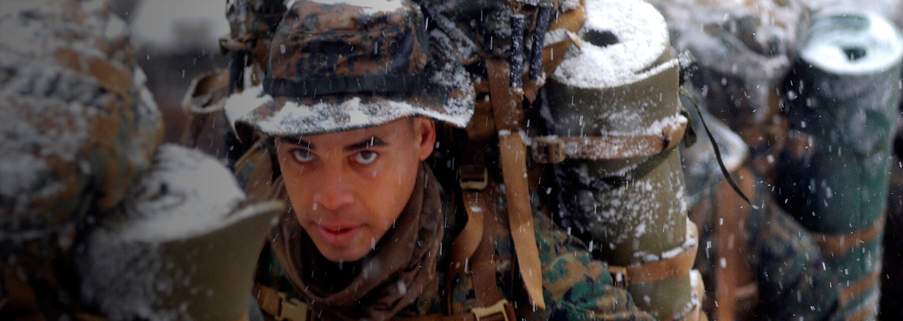 A Marine Officer marches as snow falls.