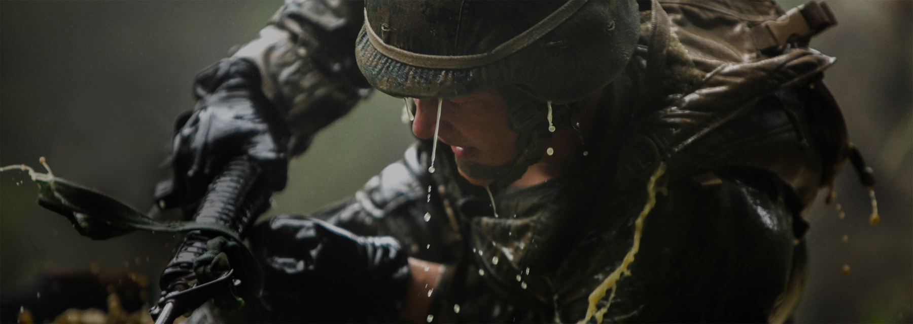 A Marine with eyes closed, water dripping from his helmet and soaked cammies pushes on with a rifle in hand.