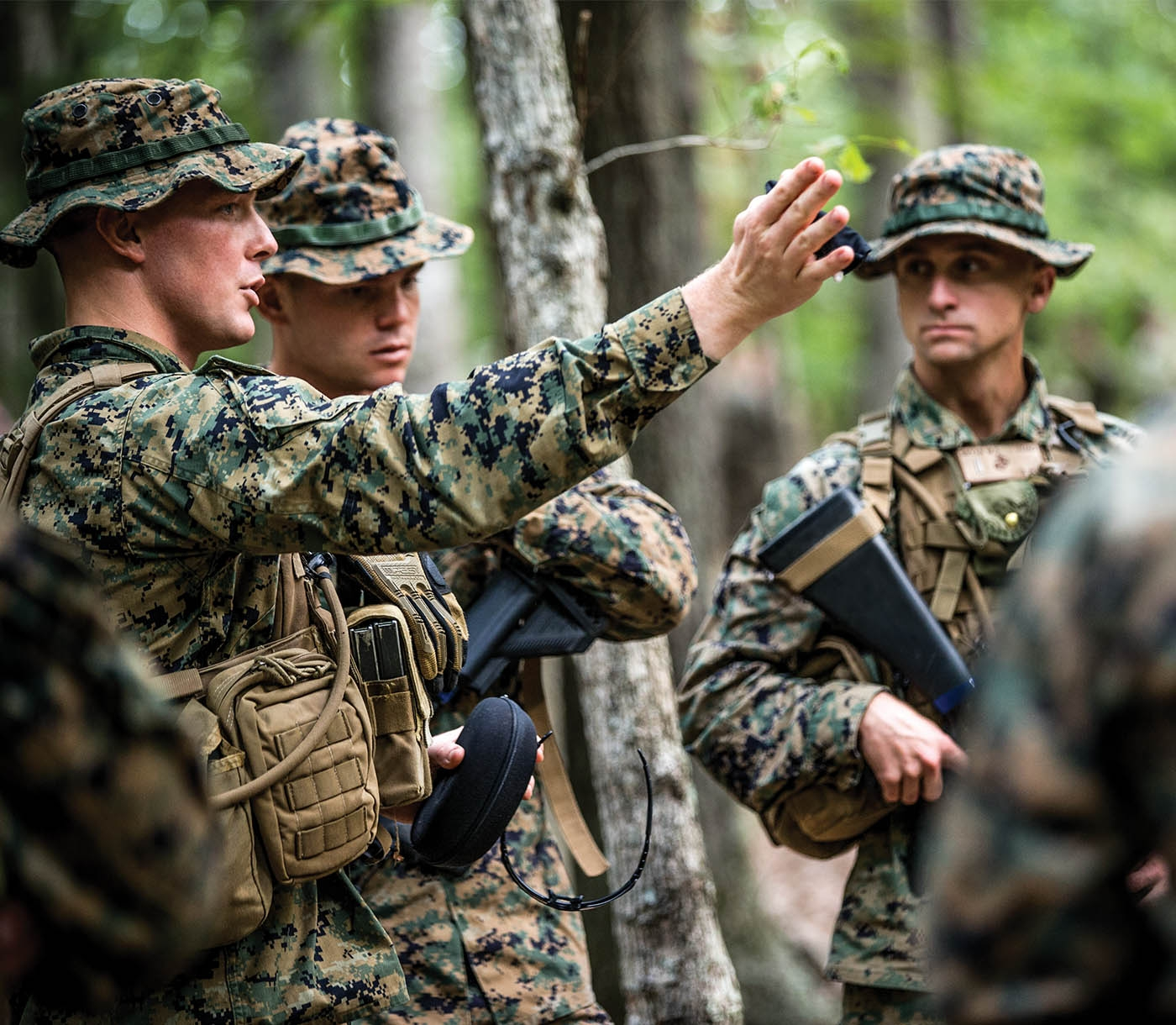 A Marine Officer gestures to other Marines to show direction.