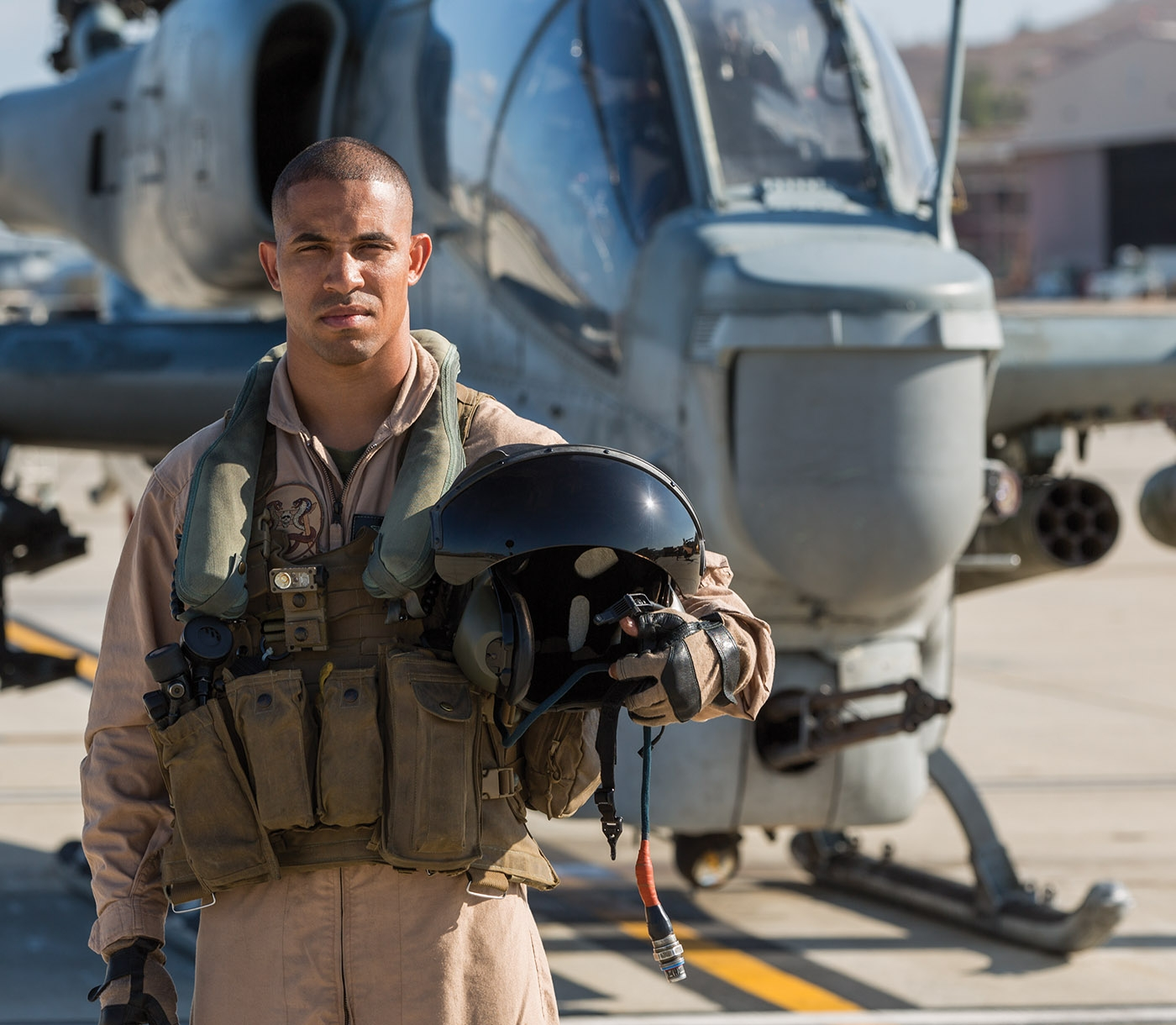 A Marine pilot stands, helmet in hand, in front of a helicopter.