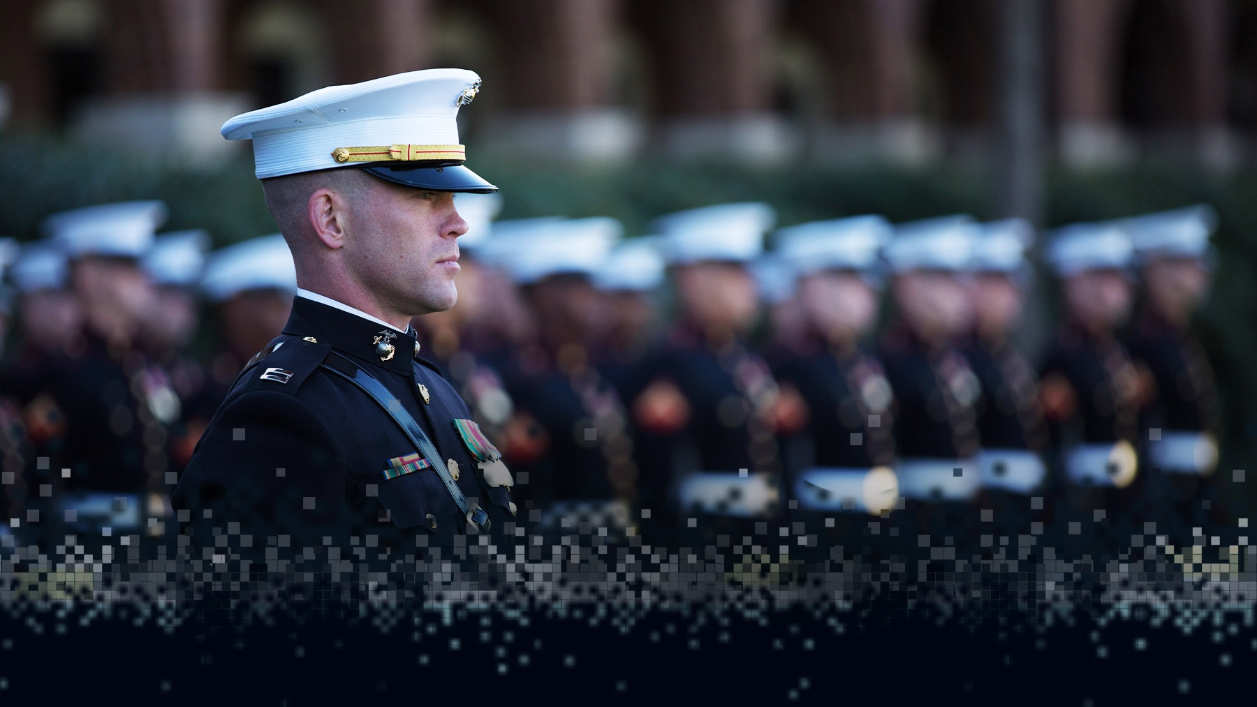 A Marine Officer in dress blues stands ahead of enlisted Marines in formation.