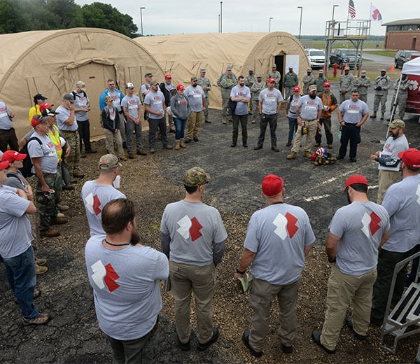 A group of Team Rubicon gray shirts receive a briefing.