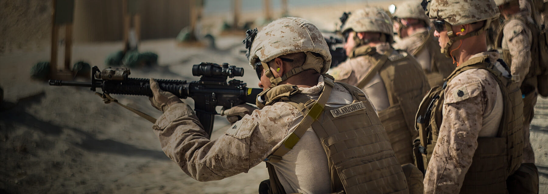 Marines participate in live fire training with assault rifles on a firing range.