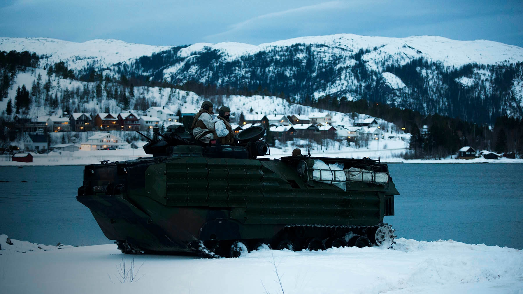Marines patrol a lake with snow-covered homes and mountains in the background.