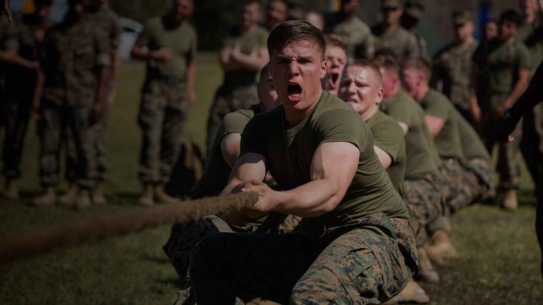 A group of Marines pulls a large braided rope during a tug of war exercise.