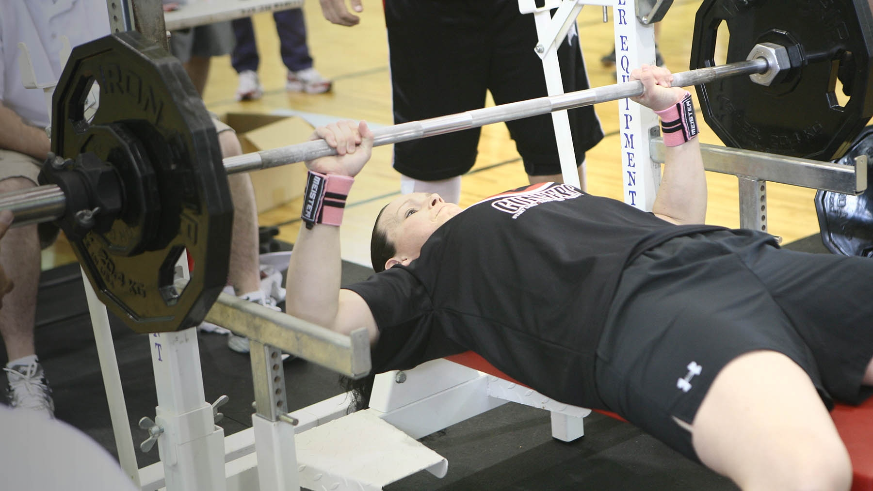 A Marine prepares to lift a weighted barbell as her spotter looks on.