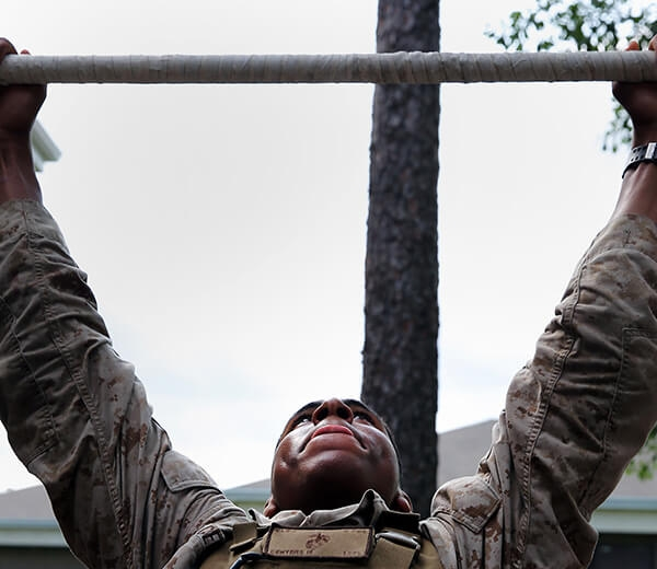 A Marine prepares to complete a pull up.