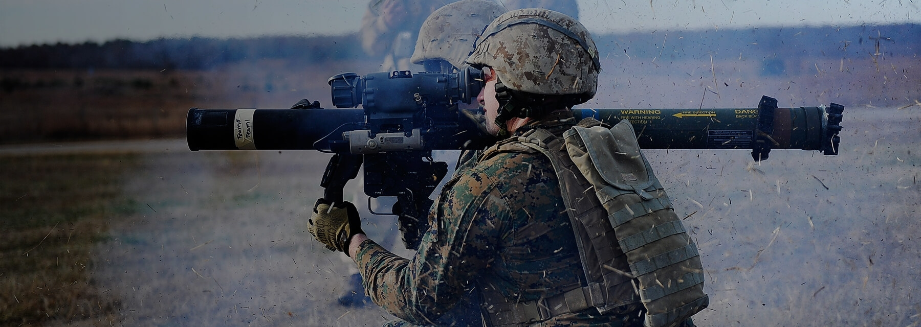A Marine fires a weapon as debris fills the air.