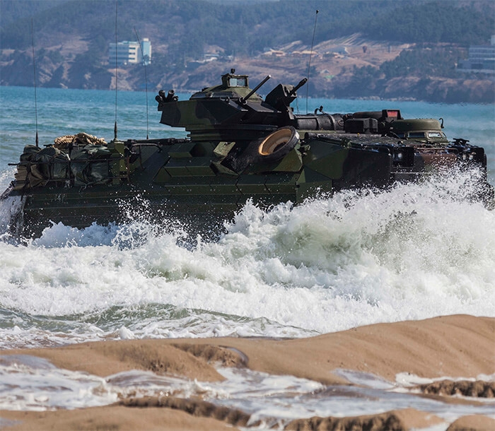 Waves crash into beach as an  Amphibious Assault Vehicle drives ashore.