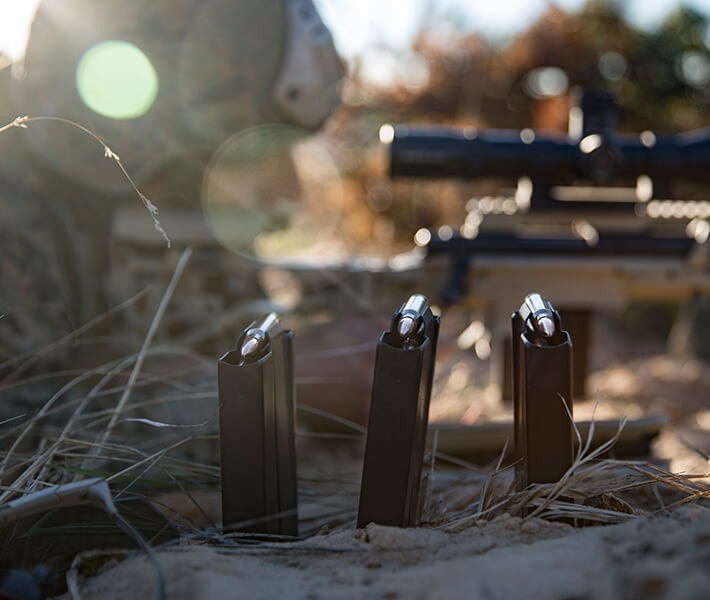 Three full magazines of ammunition are perched in the sand as a Marine Scout Sniper aims his rifle.