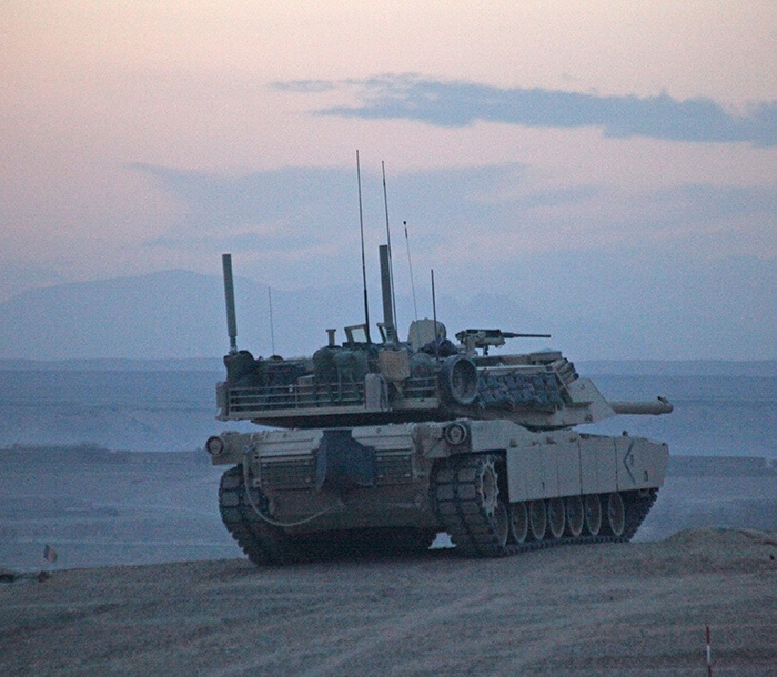 A M1A1 Tank drives into the desert as night falls.