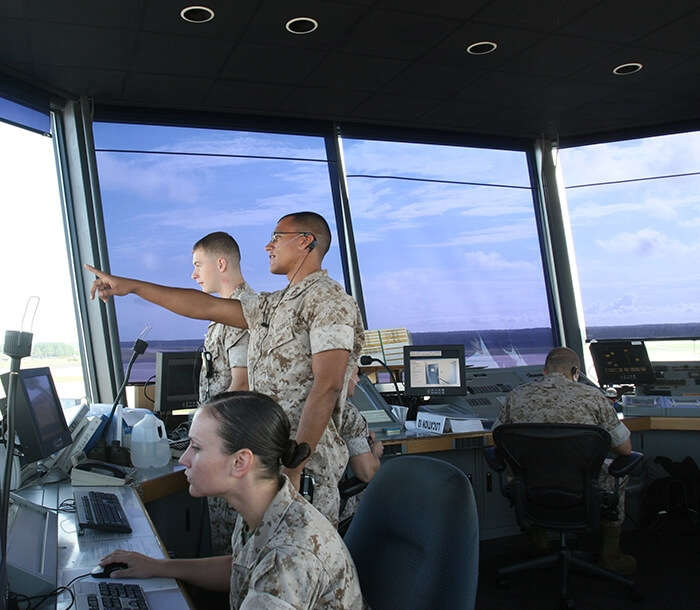 Four Marines work together in an air traffic control tower.