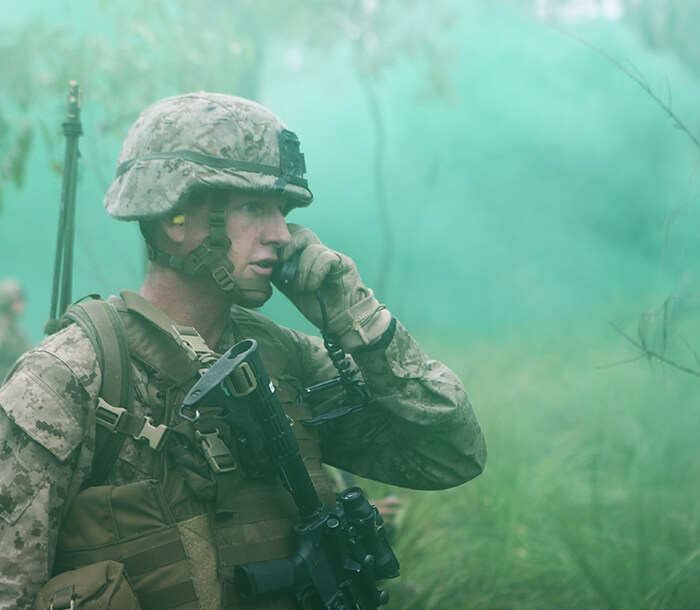 A Marine surrounded by green smoke communicates with other Marines.