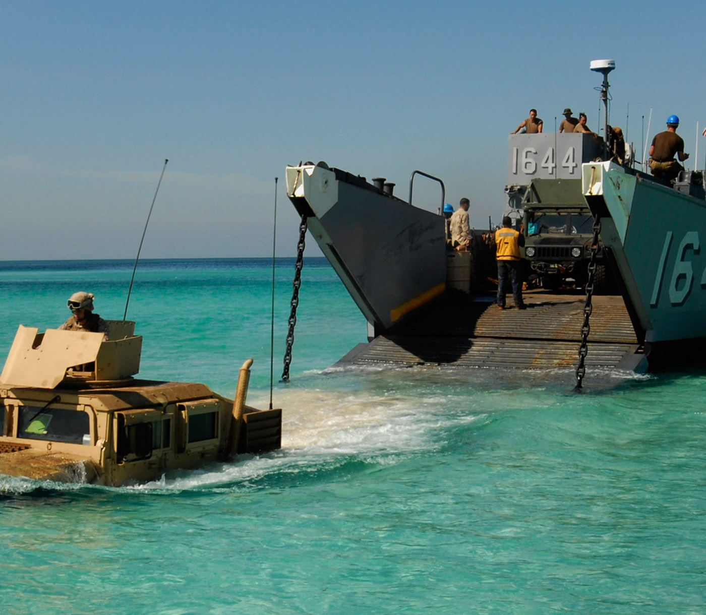 A Marine drives a Humvee into shallow, blue ocean water.
