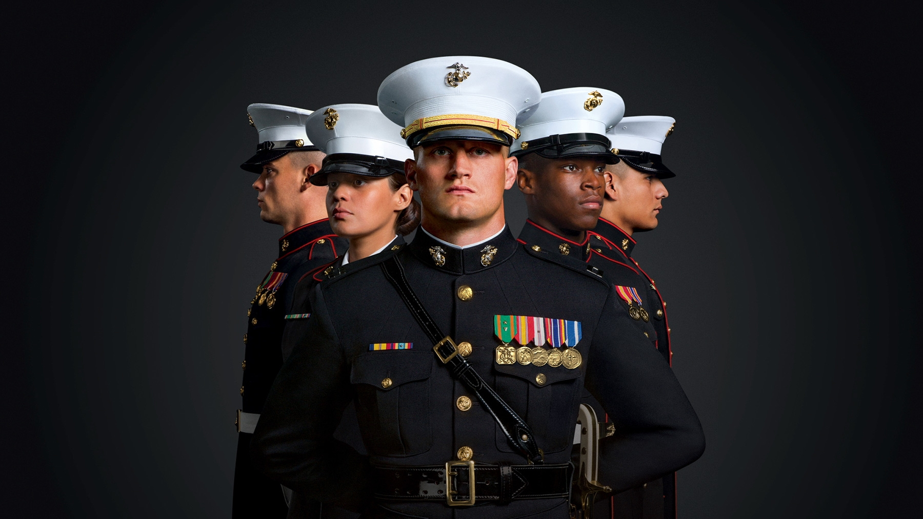 A group of Marines are shown in Dress Blues, their medals illuminated.