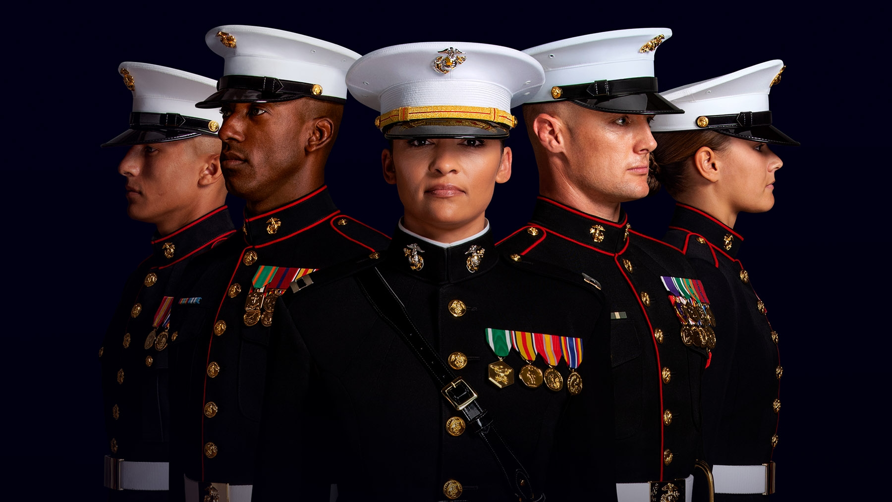 A group of Marines in dress blues stand in formation.