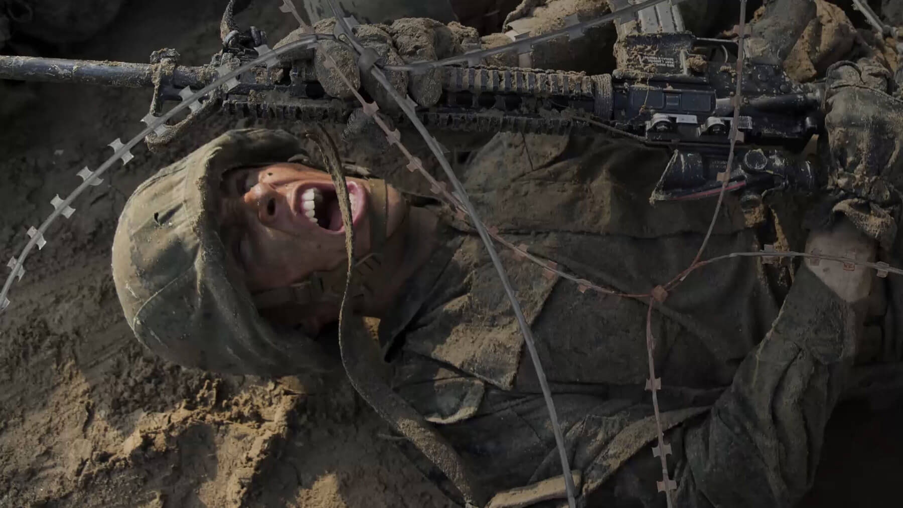 An aspiring Marine pushes himself under barbed wire during Marine Corps recruit training.