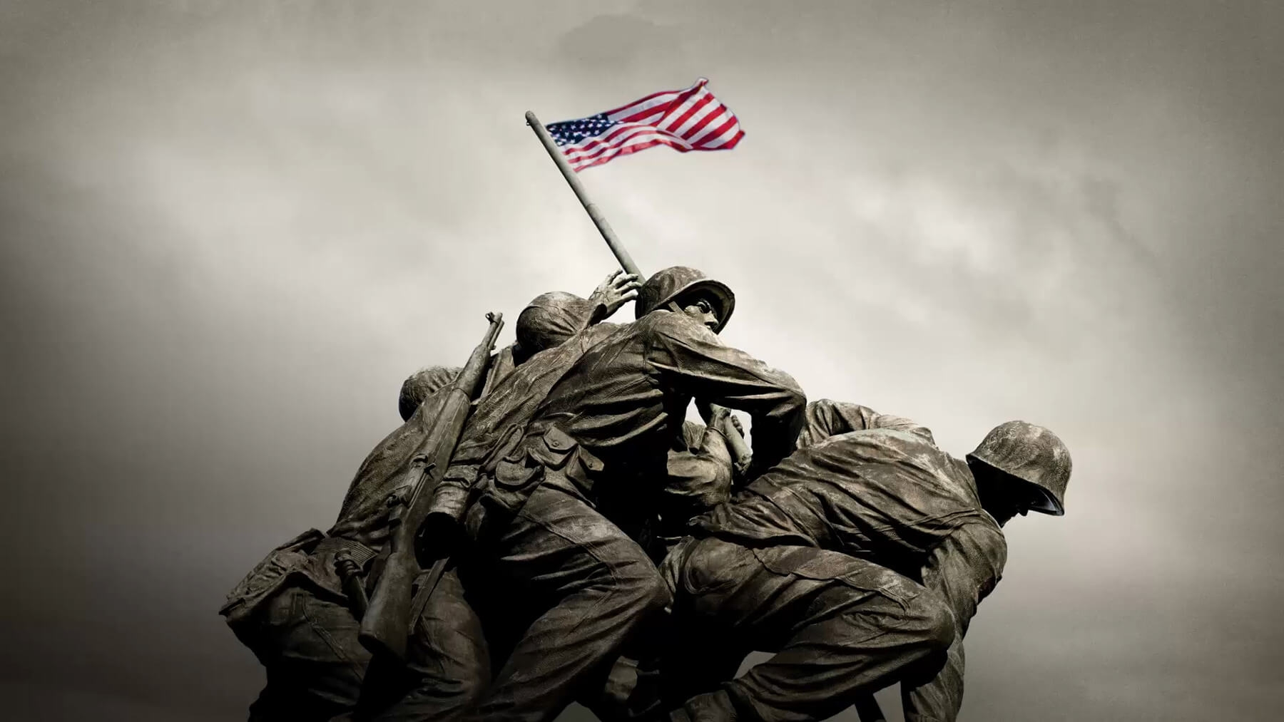 With gray skies in the background, an American flag waves in the wind atop the Iwo Jima Memorial at the U.S. Marine War Memorial in Washington, D.C.
