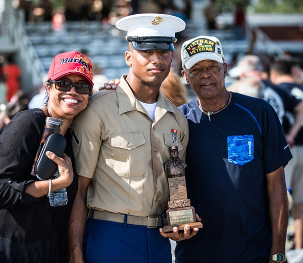 A Marine stands with his loved ones and displays and bronze award.