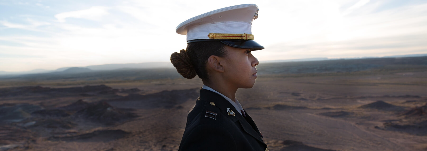 Captain Ashley McMillan looks across the Arizona desert as the sun sets in the background.