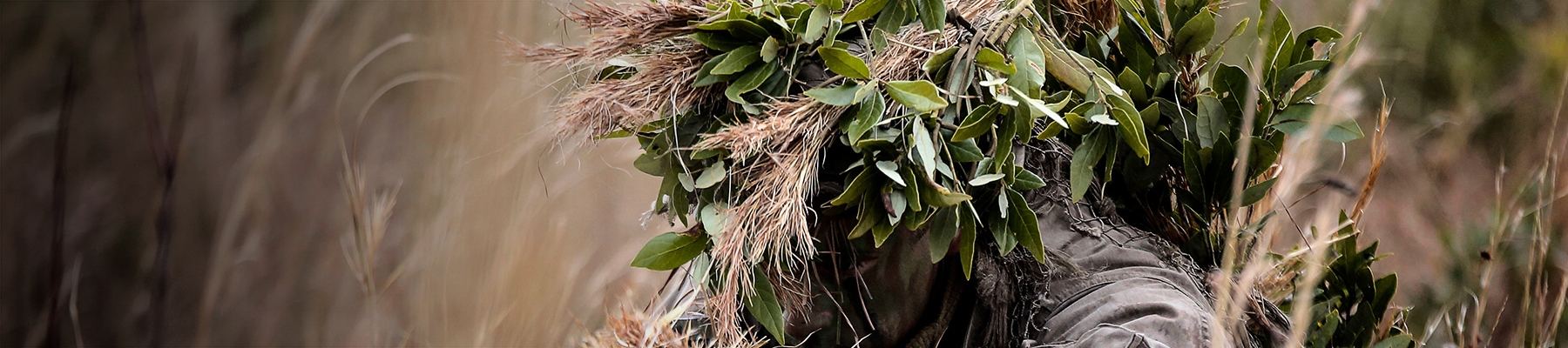 A Marine in camouflage looks out from behind leaves.