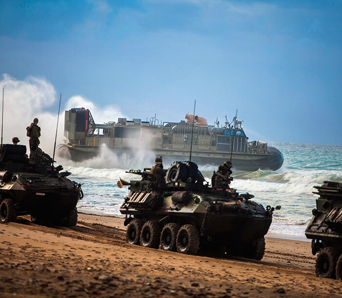 Marines in Light Armored Vehicles (LAVs) line a sandy beach.