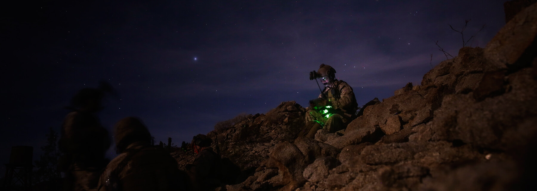 A Marine wearing night vision goggles sits atop a rocky lookout.