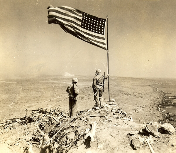 In this historical, sepia-toned photo, two Marines raise the American flag over empty battlefield.