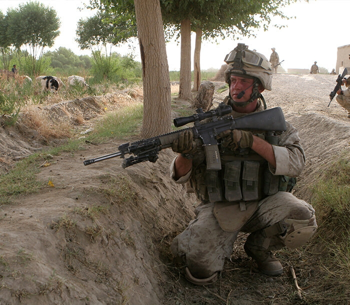 A Marine crouches in a trench with an M-16 service rifle during Operation Enduring Freedom.