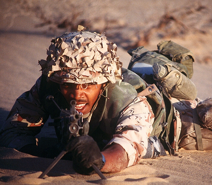 A Marine in desert cammies readies his rifle during Operation Desert Storm.