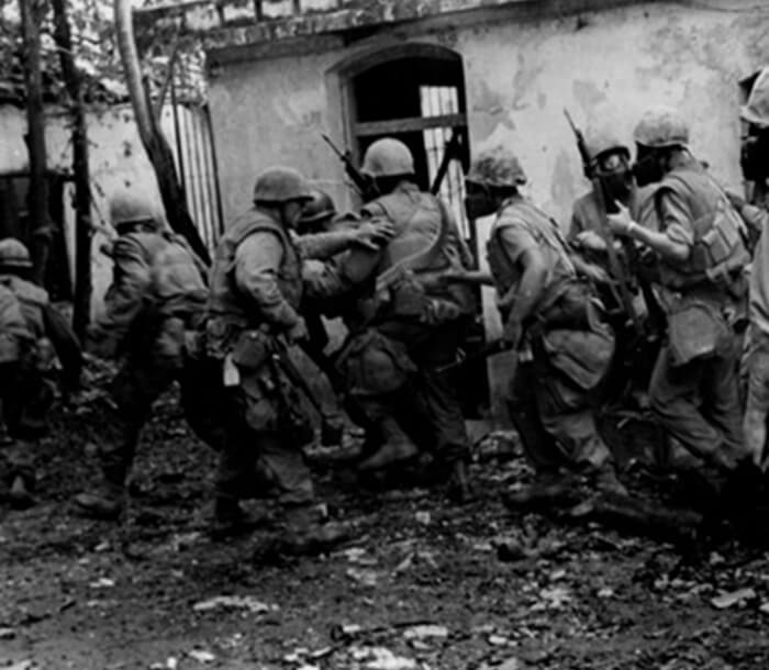 Black and white photo shows Marines moving through a neighborhood at the Battle of Hue.