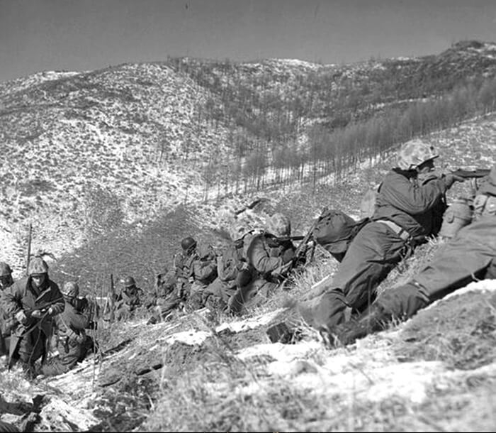 Black and white photo shows Marines on a snow-covered mountain at Chosin Reservoir.