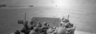 Marines approach Iwo Jima from the sea in this black and white photo.