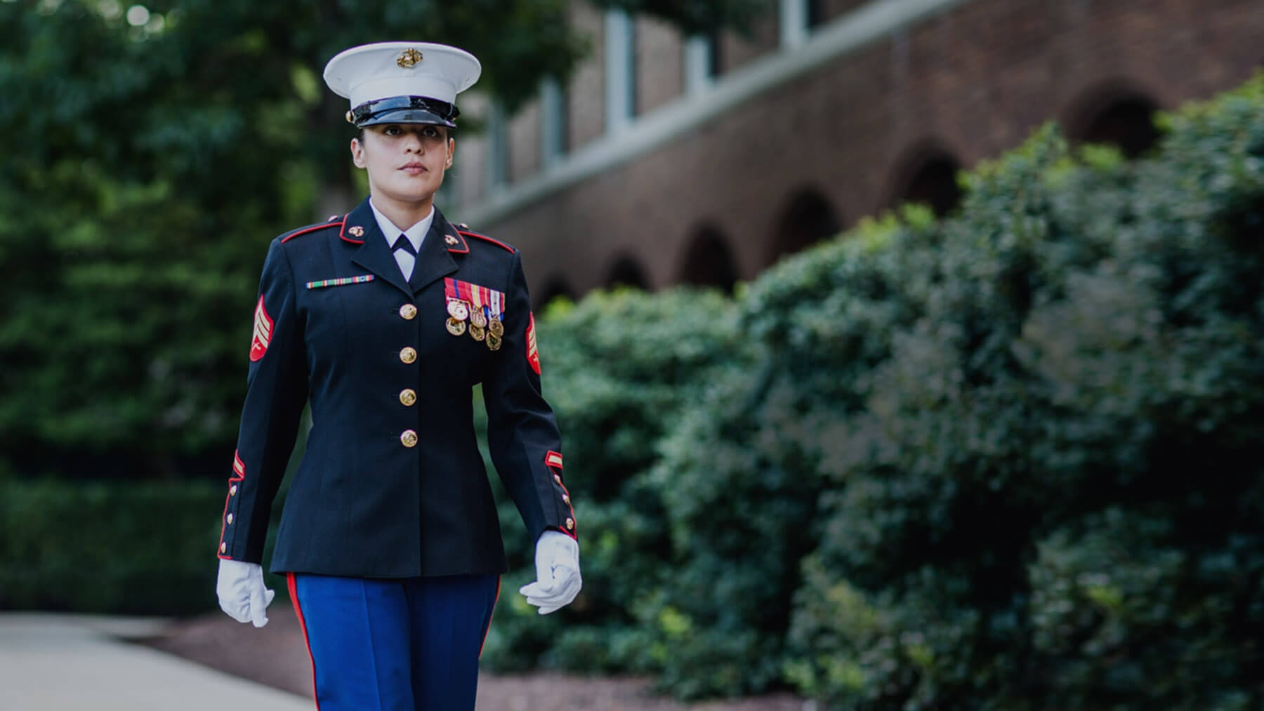 A Marine in Dress Blues and white gloves walks with a serious expression.