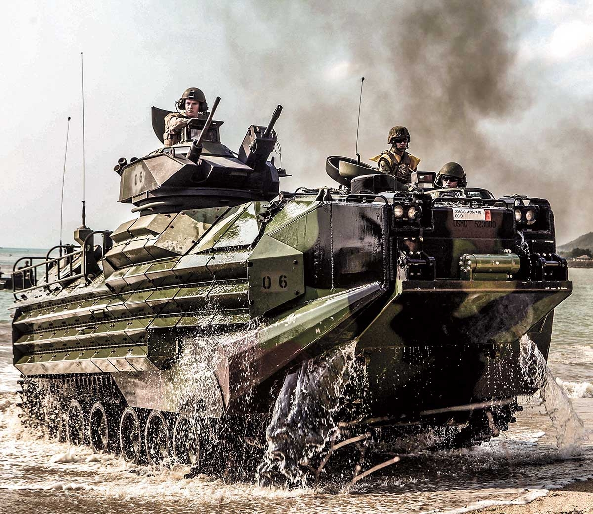 Marines in a AAV-7 Amphibious Assault Vehicle approach land as black smoke billows in the distance.