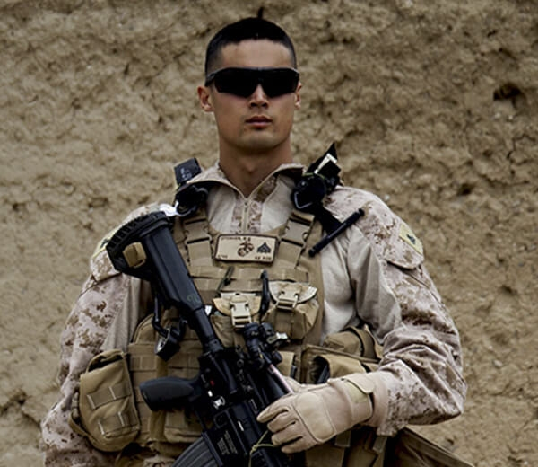 A Marine stands with hand on weapon.