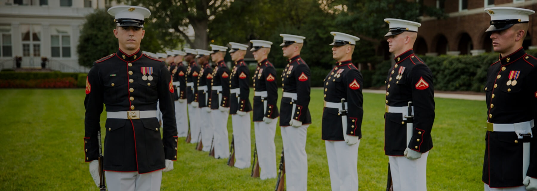 A Marine Corps Silent Drill Platoon stands in single line with rifles by their sides.