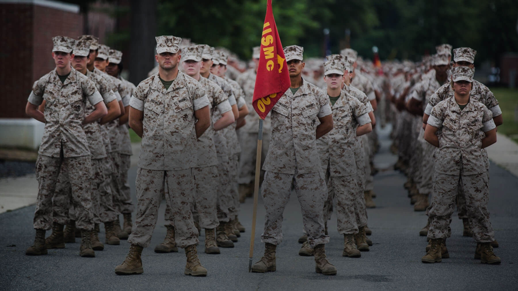 A Marine platoon stands with serious expressions.