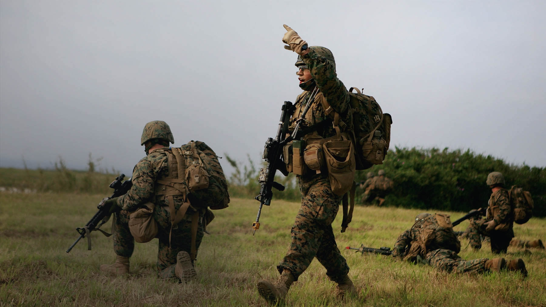 With four Marines in firing position, one Marine stands and gives commands to lead the team forward.