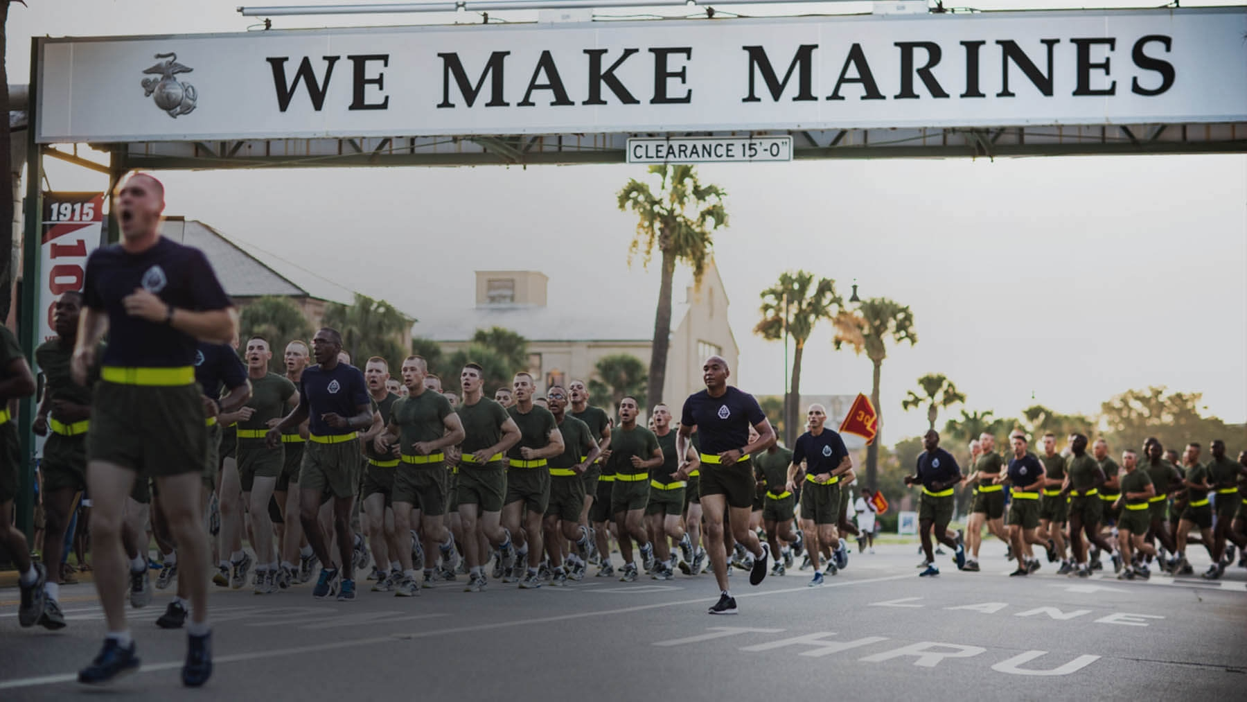 A large group of Marines run cadence together.