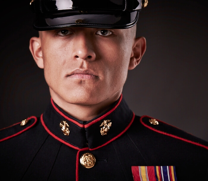A Marine in dress blues wears the Eagle, Globe and Anchor emblem.