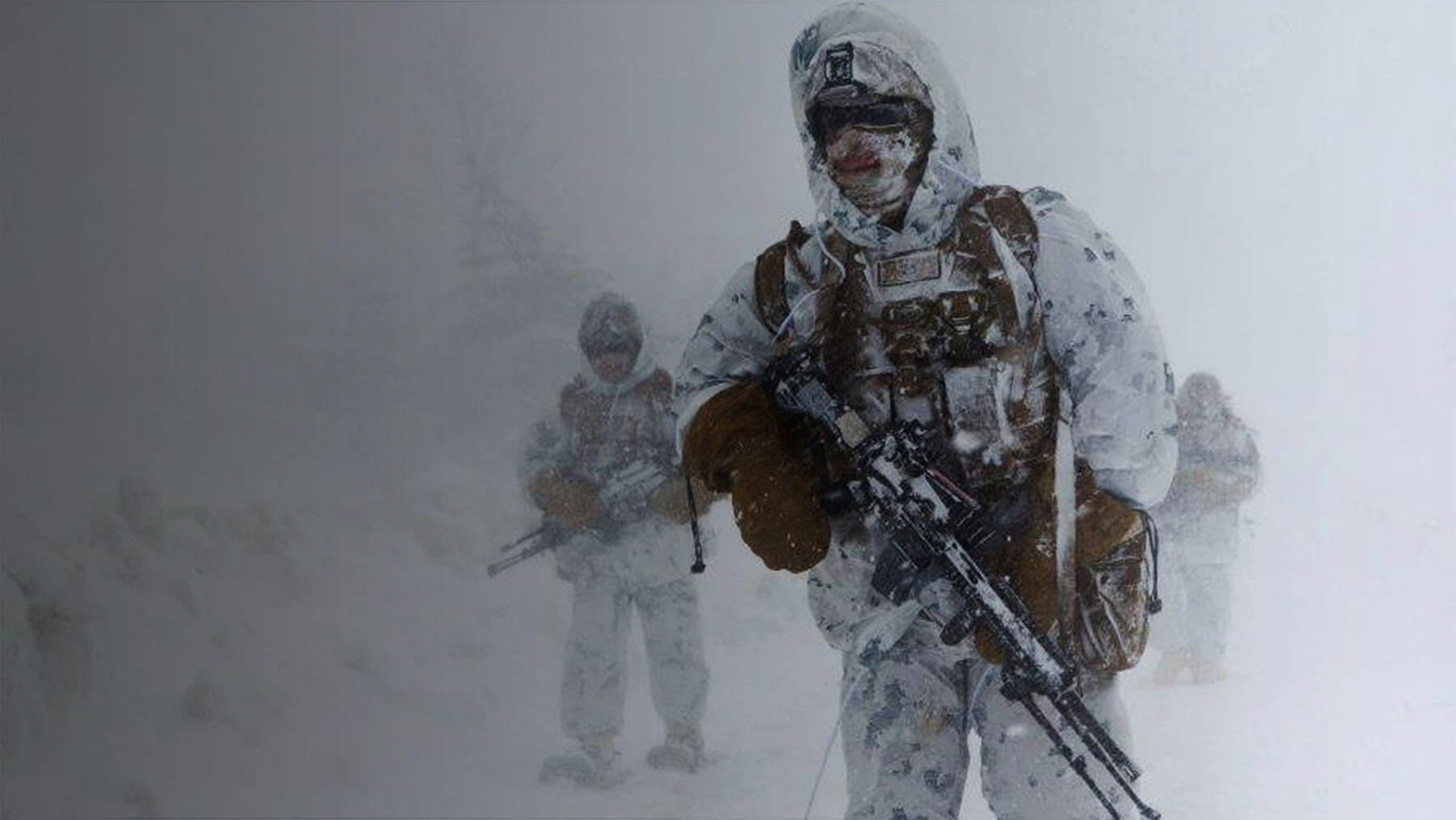 Marines in white and gray patterned cammies walk in heavy snow.