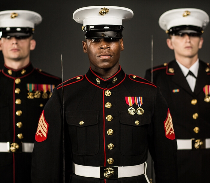 A group of three Marines are showing in dress blue uniform.