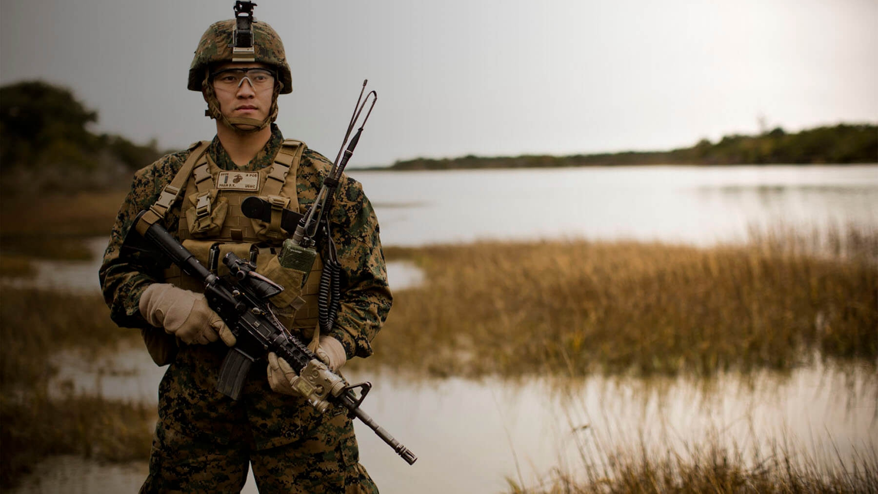 A Marine dressed in Combat Utility Uniform stands near a marsh.