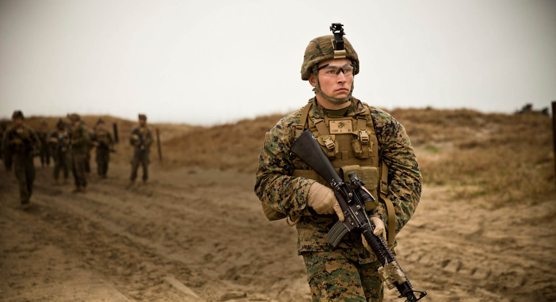 A Marine dressed in Combat Utility Uniform patrols with his M-16 service rifle.